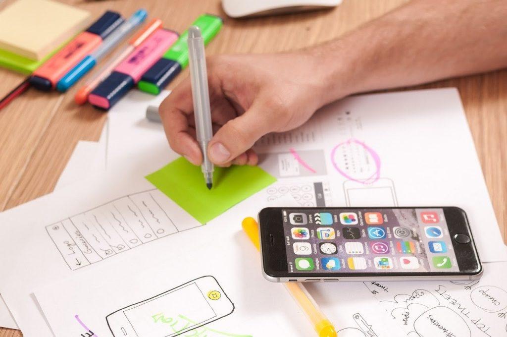 Рабочий стол с айфоном, человек пишет на листке заметки