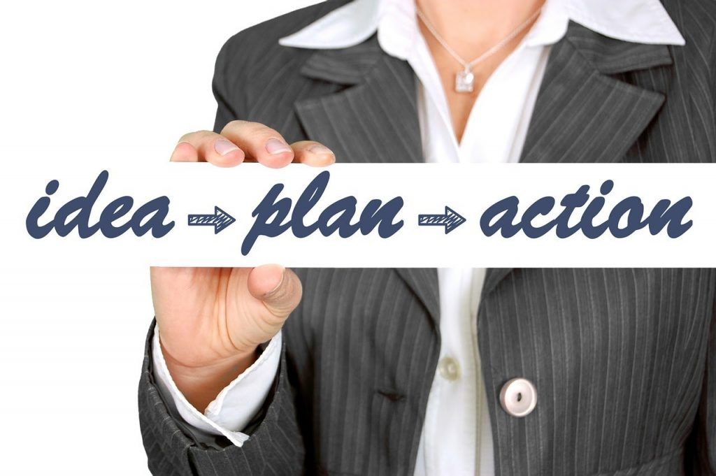 Женщина держит в руках табличку: идея-план-действие